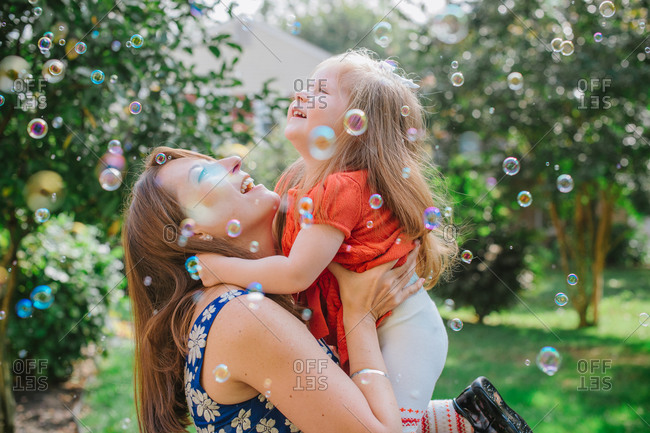 Toddler girl laughing as she is held by her mother and surrounded by bubbles