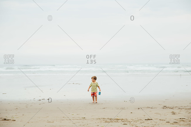 Boy holding a watering can and walking along the beach
