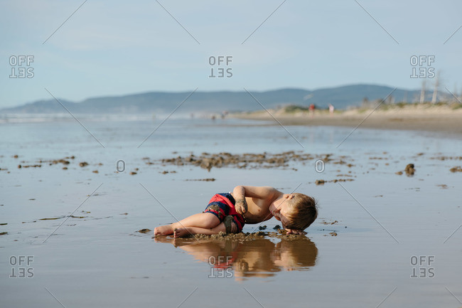 Boy digging in the sand on the beach