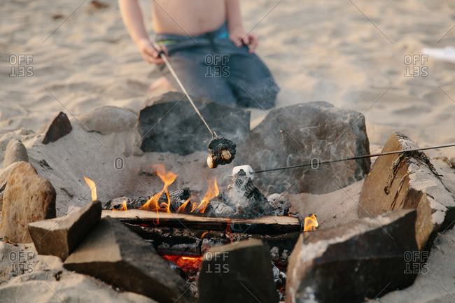 Boys roasting marshmallows at the beach