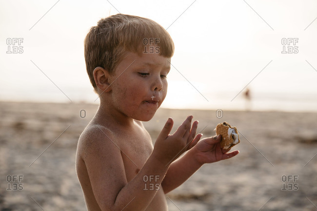 Boy eating a roasted marshmallow at the beach
