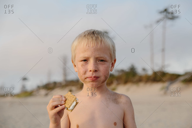 Boy eating a s'more at the beach