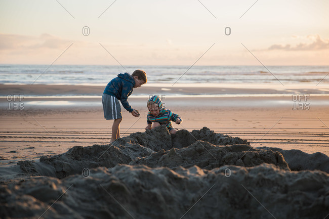 Boys digging in the sand on the beach