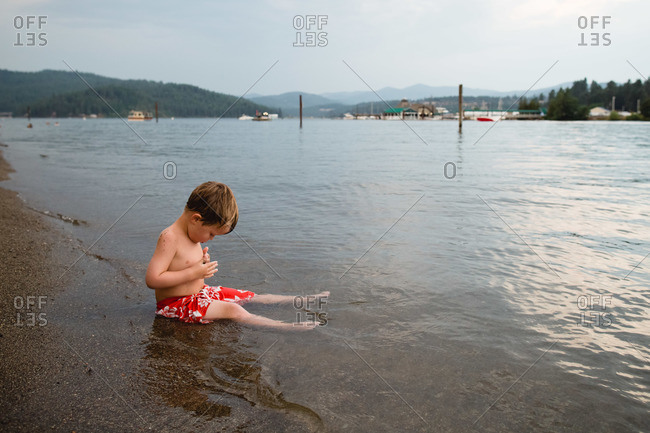 Boy sitting in the water along a lakeshore