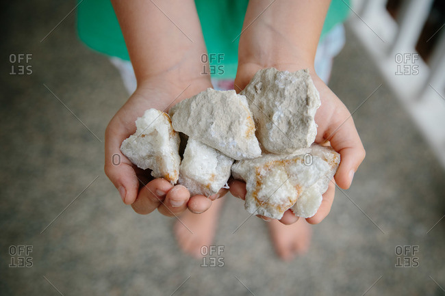 Child holding a handful of geodes