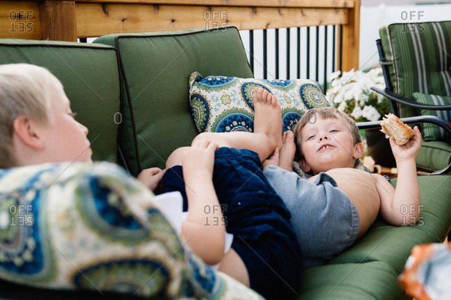Two boys lying down on the couch together and roughhousing