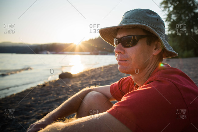 Man wearing sunglasses and a hat sitting outside on a beach at sunset
