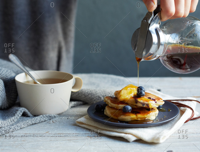 Person pouring syrup on blueberry pancakes
