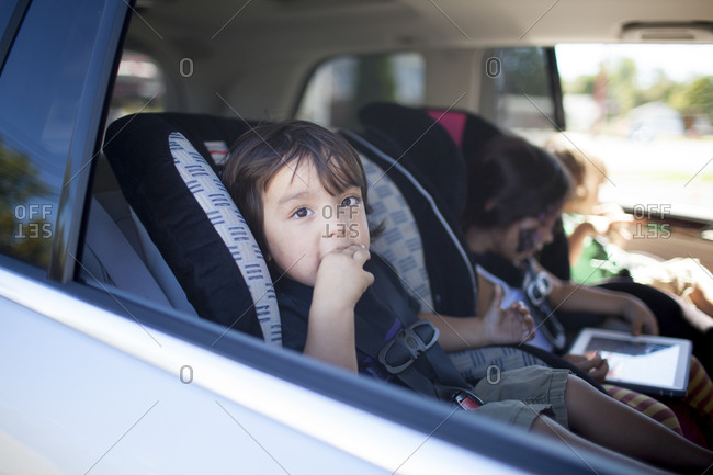 View through vehicle window of children in car safety seats
