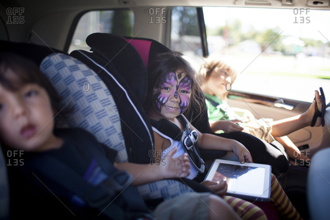 Girl with painted face sits in car seat between two brothers
