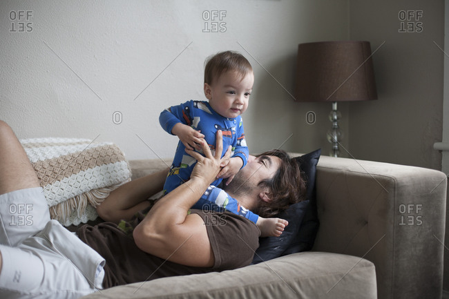 Man holding his toddler son while lying on couch