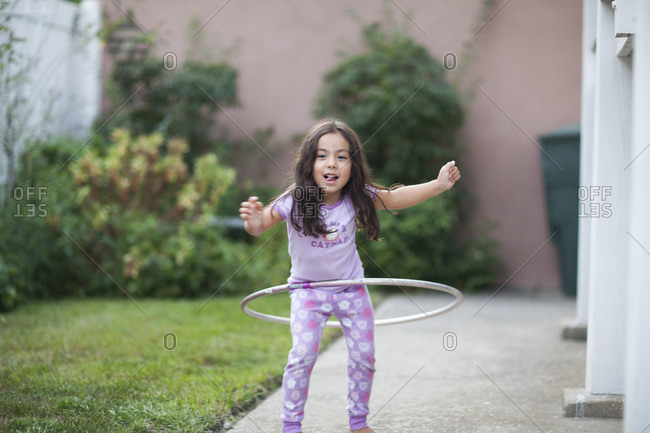 Young girl playing with a hula hoop on sidewalk
