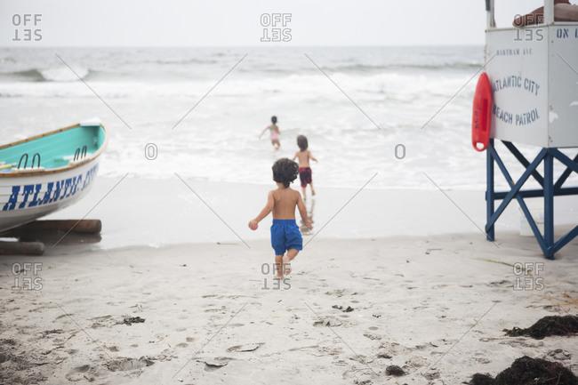 Children running to the ocean near lifeguard stand