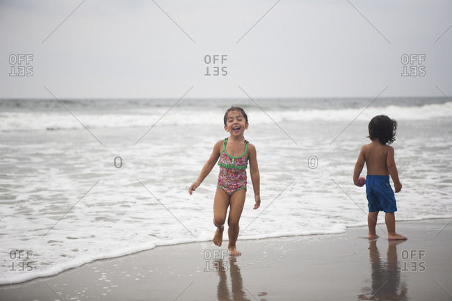 Young girl running on beach with brother nearby