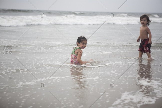 Girl and boy playing in ocean waves