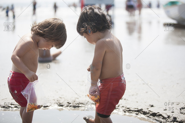 Twin boys playing in puddle on beach