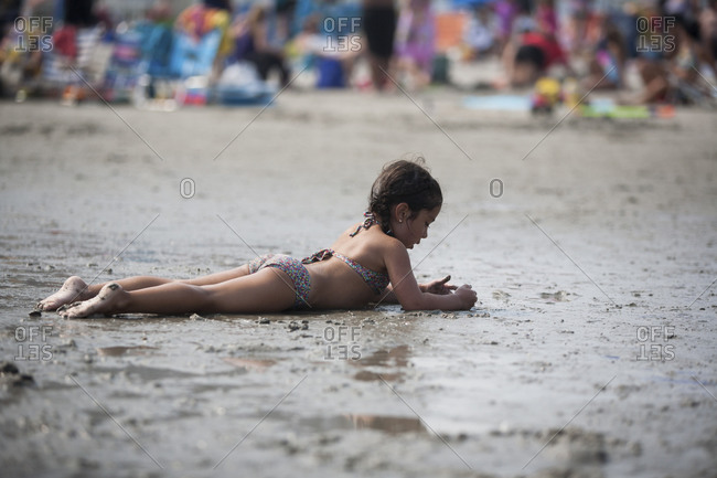Young girl lounging on wet sand at beach
