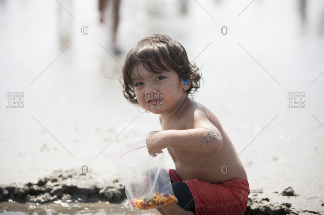 Toddler boy crouched in pool of water with snack on beach