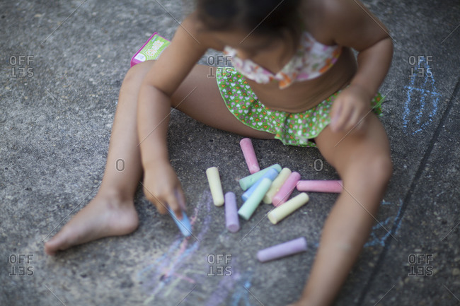 Elevated view of young girl drawing on pavement with chalk