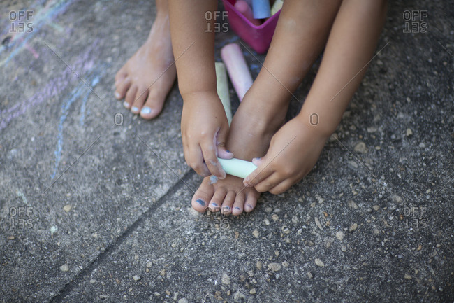 Child drawing on her feet with chalk