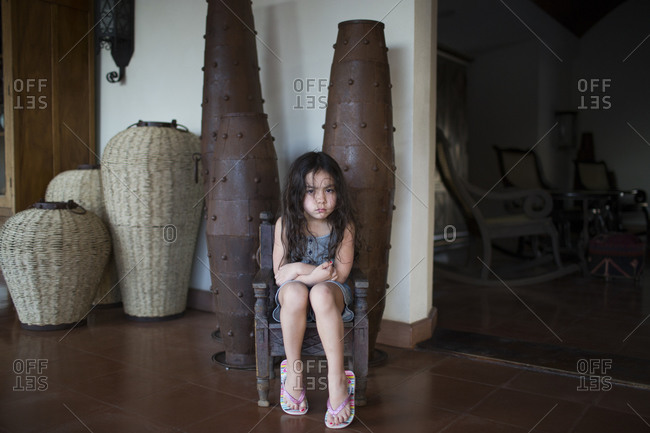 Angry young girl sitting in chair