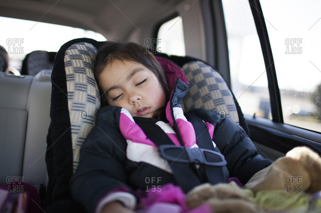 Young girl asleep in car seat
