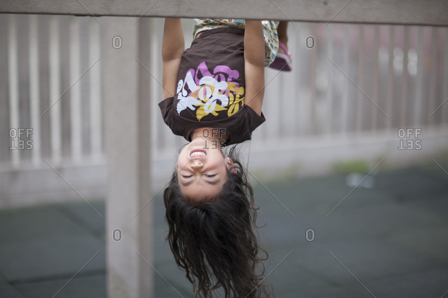 Portrait of young girl hanging upside down on monkey bars