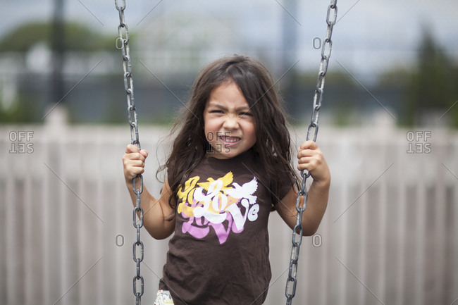 Portrait of young girl playing on swing