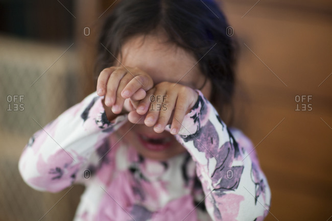 Crying young girl covering her eyes