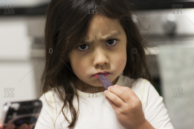 Unhappy young girl eating a snack