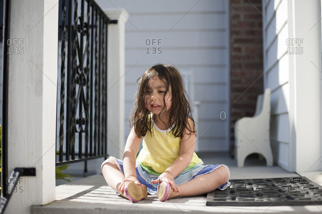 Sad toddler girl sitting on porch