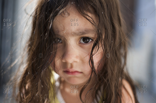 Close-up portrait of toddler girl with water droplets in her hair