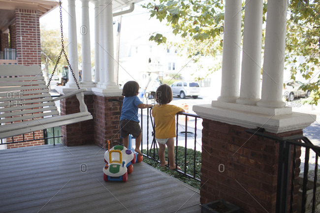 Twin toddler boys standing on front porch railing