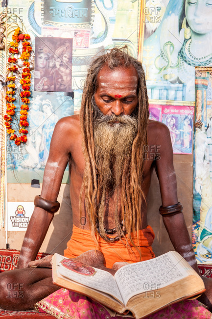 Varanasi, India - February 4, 2016: A Hindu holy man reading a book