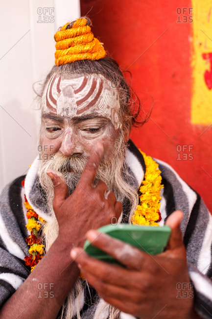Varanasi, India - February 5, 2016: A sadhu applying paint to his face