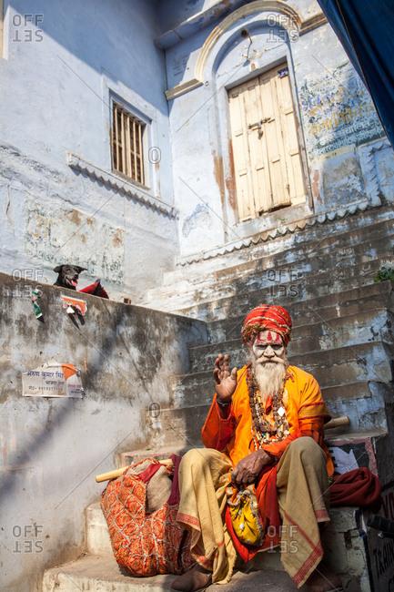 Varanasi, India - February 5, 2016: Hindu man sitting on steps waving