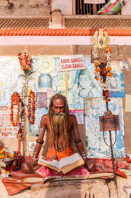 Varanasi, India - February 4, 2016: A Hindu holy man with dreadlocks sitting on a mat reading