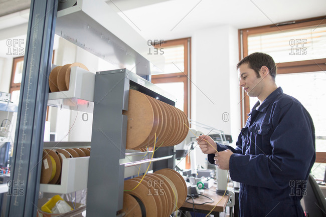 Male electrician pulling power cable from cable drum in workshop