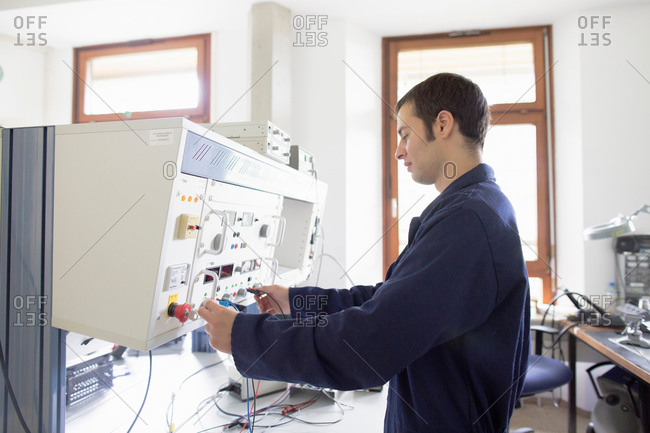 Male electrician testing control panel workshop