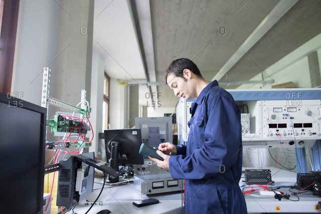 Male electrician repairing control panel in workshop