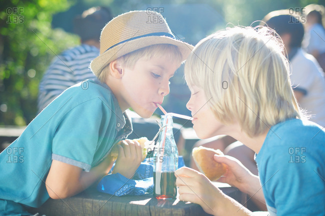 Two young boys drinking from bottle with straws