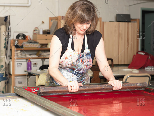 Woman hand-printing textile in a studio