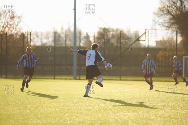 Soccer player kicking a high ball