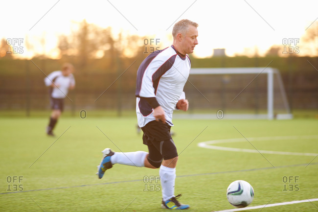 Older soccer player with possession of ball