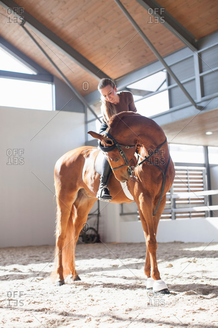 Mid adult woman on chestnut horse in indoor paddock