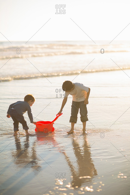 Brothers filling toy truck with seawater on beach