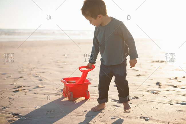 Boy pulling toy truck filled with sand along beach