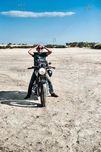 Mid adult man sitting on motorcycle on arid plain