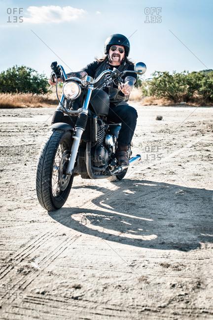 Mature man motorcycling across arid plain