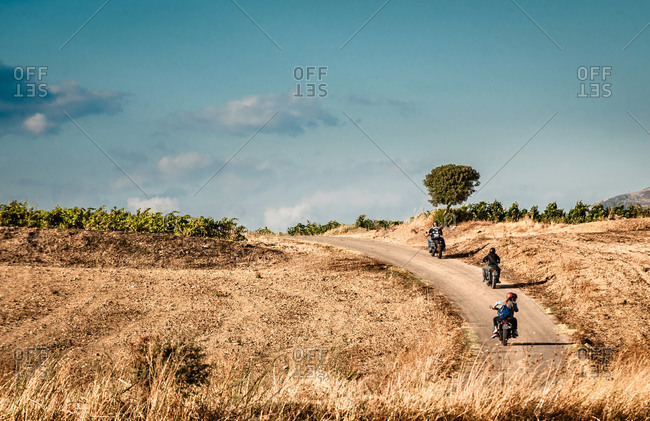Rear view of four friends riding motorcycles on rural road